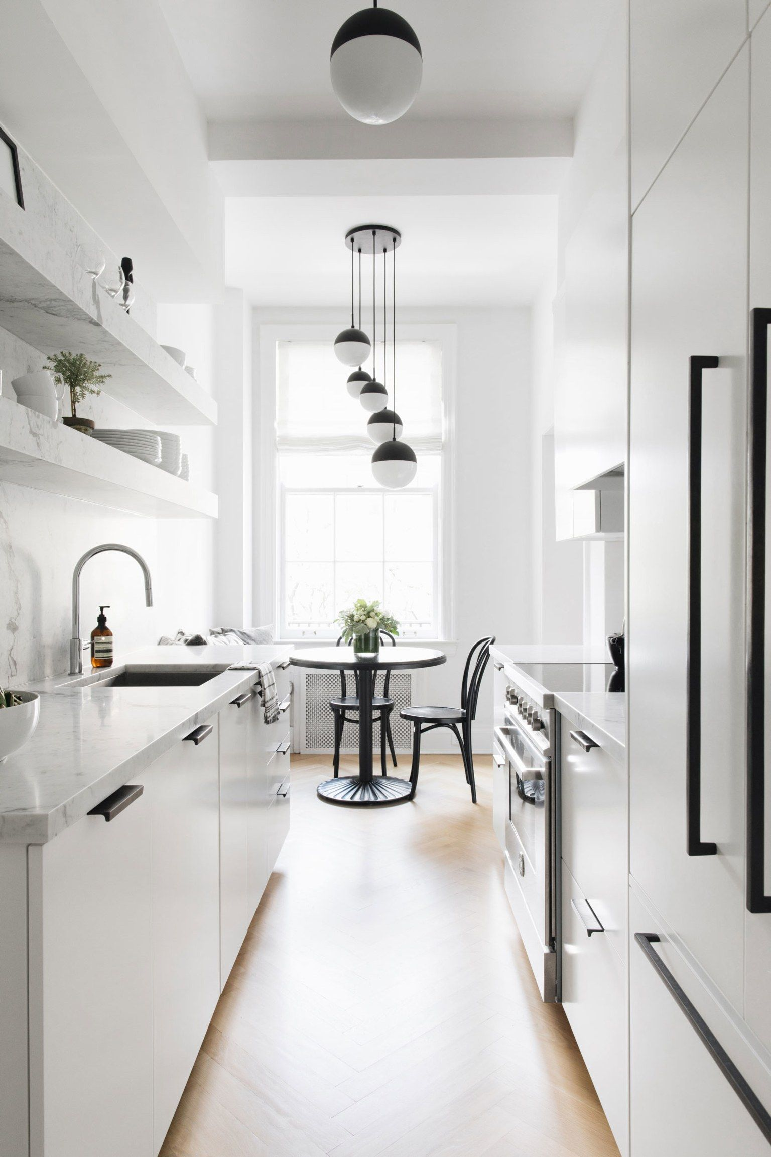 white and marble galley kitchen with breakfast