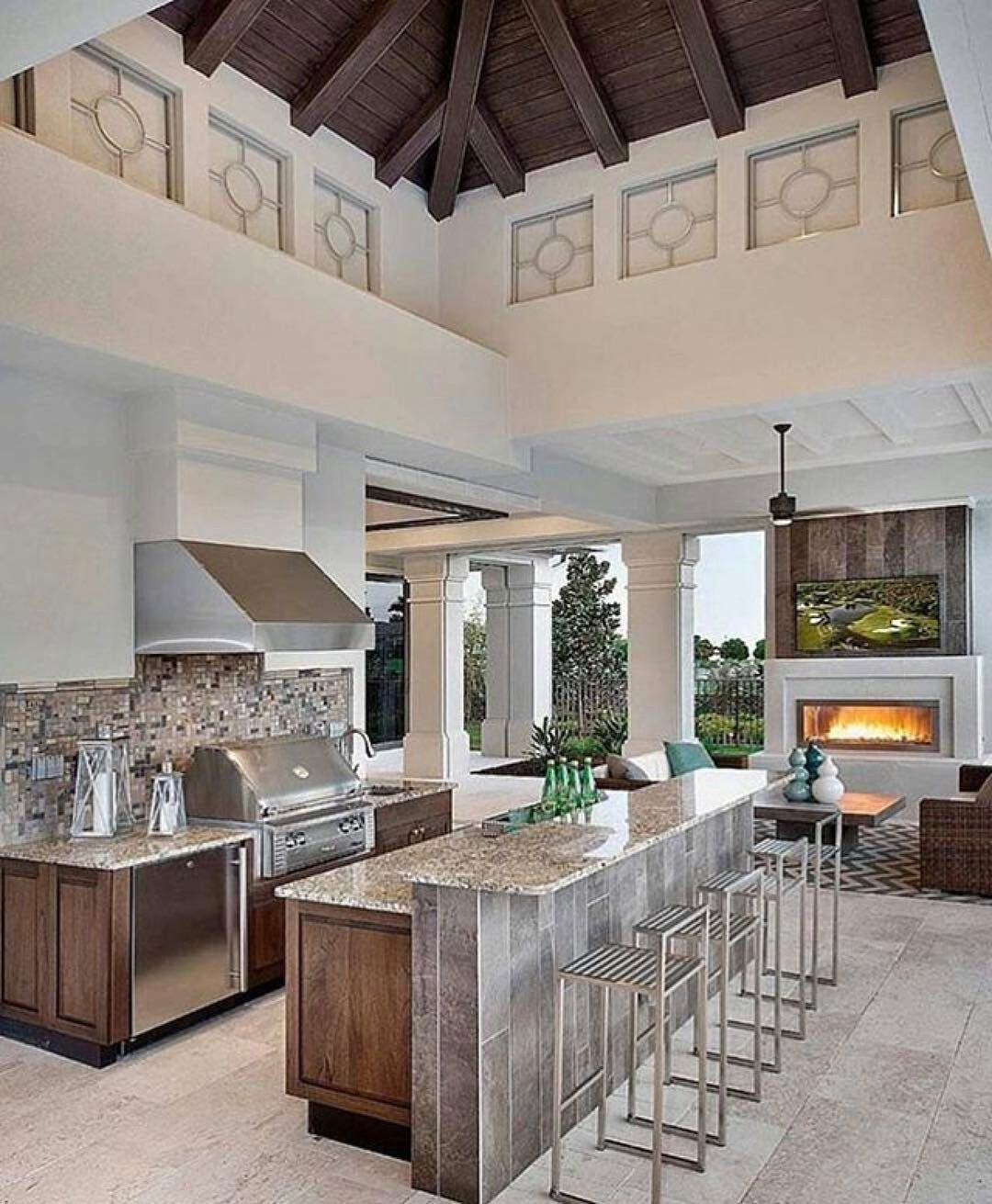 Covered outdoor kitchen with fireplace and dining area. | Pools ...