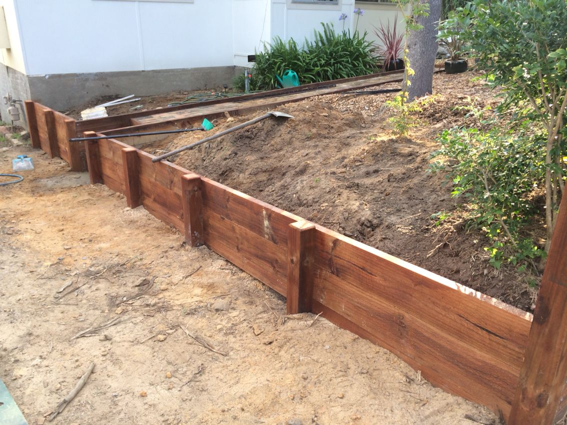 diy timber retaining wall in the making treated pine lengths with a jarrah stain - Timber Retaining Wall Designs
