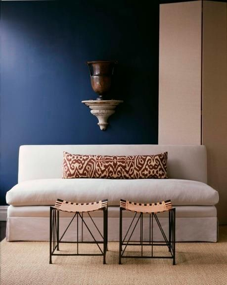 Lovely simple arrangement, ikat against dark navy. Custom sofa ~ Anthony Todd in AD