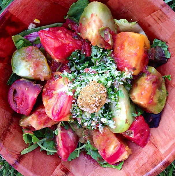 Perfect Summer Salad  ! Heirloom tomatoes over a bed of greens, taboule and a raw vegan falafel on top !