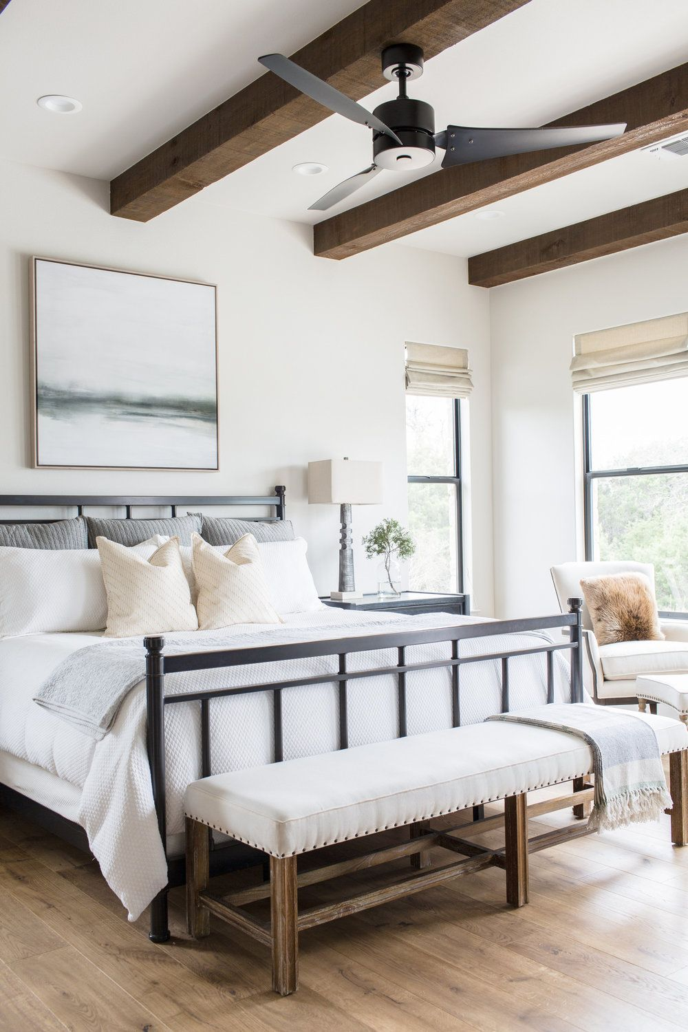Wood beam detail + exposed beams + bench at end of bed + black metal bed frame + tri-blade fan + black ceiling fan + art above bed + white linens + accent chair | Daley Home Design #modernfarmhousebedroom