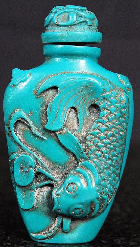 A decoratively carved chinese perfume / snuff bottle raised in relief with carp having Chinese character marks to verso