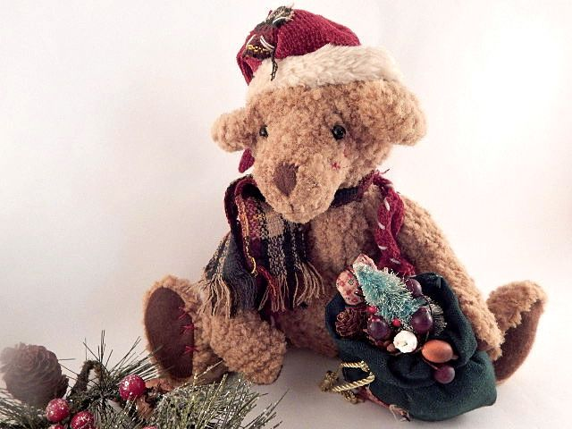 """Rustic nubbly brown stuffed bear Dressed with a patched  Santa hat and plaid scarf Felt paws and charming face with embroidered nose and sewn in eyes Holding a green fabric sack of miniature gifts and pine cones Bear in sitting position measures 10"""" ..."""