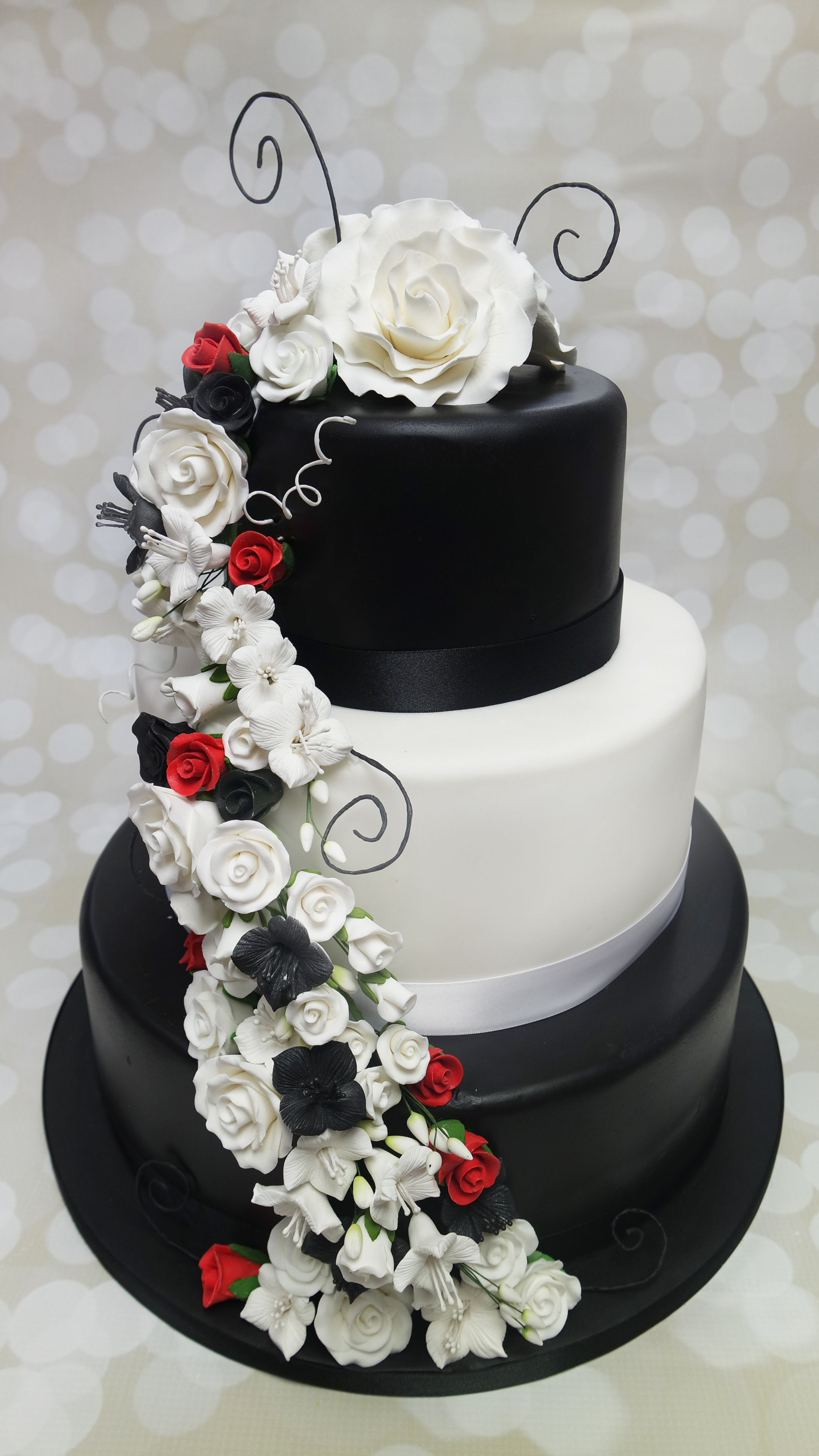 Elegant black and white wedding cake with a hint of red