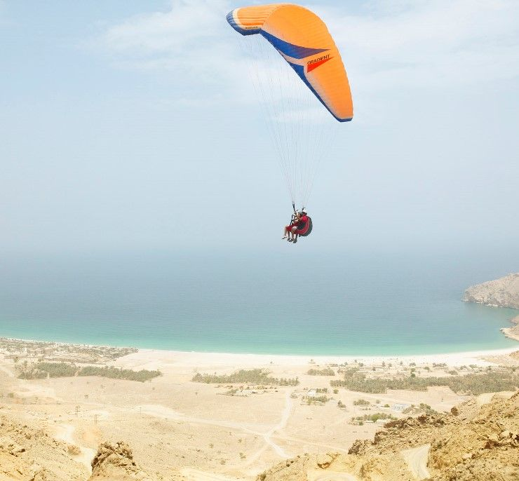The ultimate adrenaline rush: paragliding down to the beach at Zighy Bay in Oman