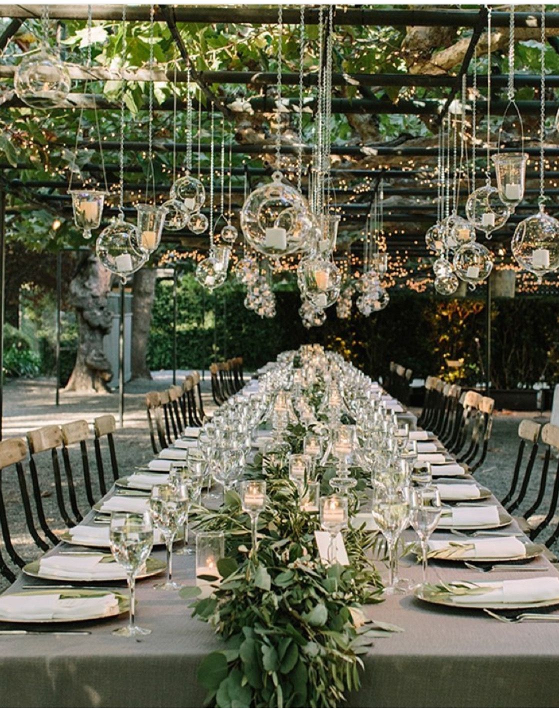 Garden event decor  wedding decor  garlands along table  hanging votives and lights