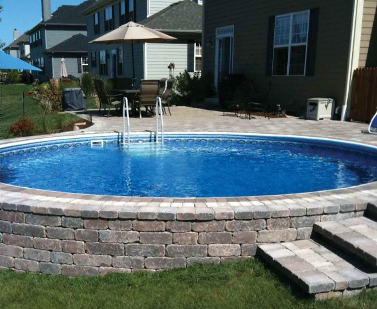 a paver wall around an above ground pool what a neat idea bet it would cost just as much as an in ground pool once you finished the pavers