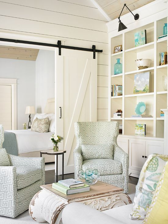 love these greek key patterned chairs, the barn door, and the wall of shelving