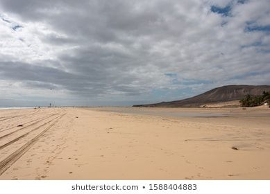 Sotavento beach during low tide Cloudy sky kite surfers in the background Fuerteventura Canary Islands ocean surfing sotavento el paso
