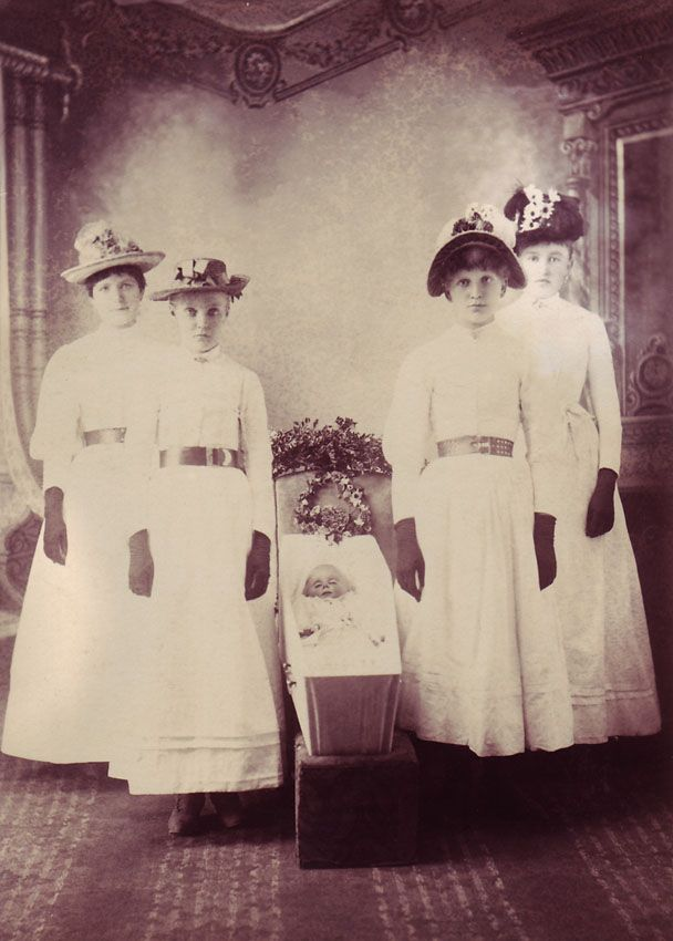 An unusual post mortem portrait showing four young women, probably sisters of the deceased child, standing at the four corners of an infant's open coffin. The women are all dressed in a pale colour, presumably white, and each is wearing a hat and a pair of dark gloves.    Photographer and location unidentified, but almost certainly American in origin.