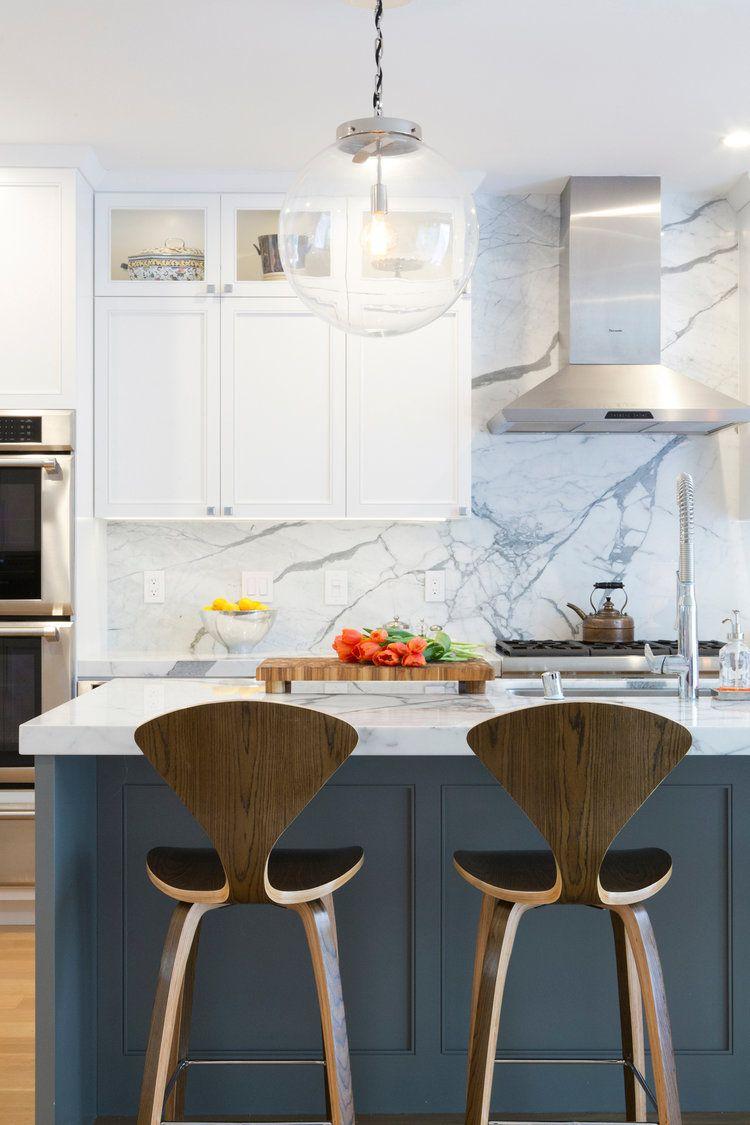 Amazing kitchen design with white marble back splash, dark island cabinets and wooden bar stools | Jack Ryan Design