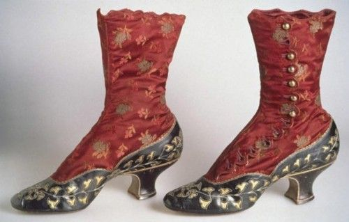 """Boots: 1883, high-button style of silk satin brocade with kidskin vamp, quarter, and baby French heel, kidskin decorated with cut-out pattern of rhododendron leaves underlaid with gold-colored kid, scallop-edge closure along side with circular brass buttons."
