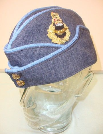 This is a mint unissued condition British, RAF 'Ranking' Senior Officer's Flight Rank Side Cap. It's Air Force Blue material with sky blue piping is totally clean and undamaged. The front of the cap is mounted with 2 gilt buttons embossed with 'Crown and Eagles in flight'. The right side of the cap features a superb embroided RAF badge with gold thread and laurel wreaths with red, gold and stitched gem stone design Queen's Crown surmounted by a Lion. Militaria