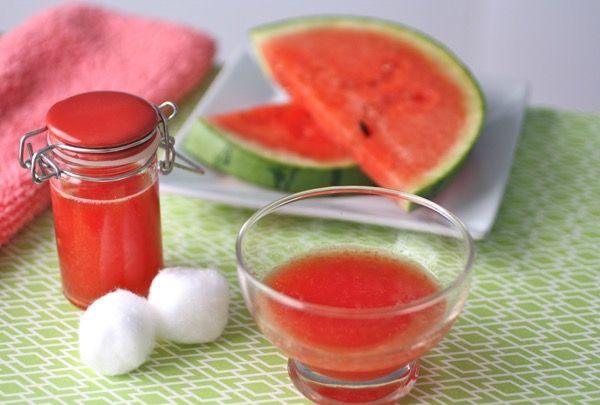 Görögdinnye levéből készült arcfrissítő piros tetejű üvegcsében, mellette vattapamacsok, puha törülköző és vékonyra szelt görögdinnyék.