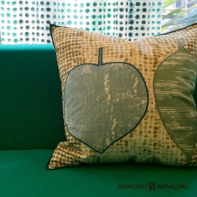 Composição de produtos Designers Guild: almofada sobre sofá com tecido de cortina ao fundo.