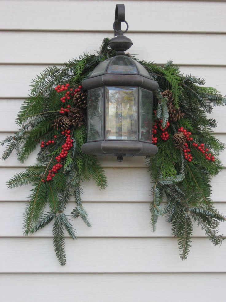 Evergreen swag with berries and lantern christmas decorations