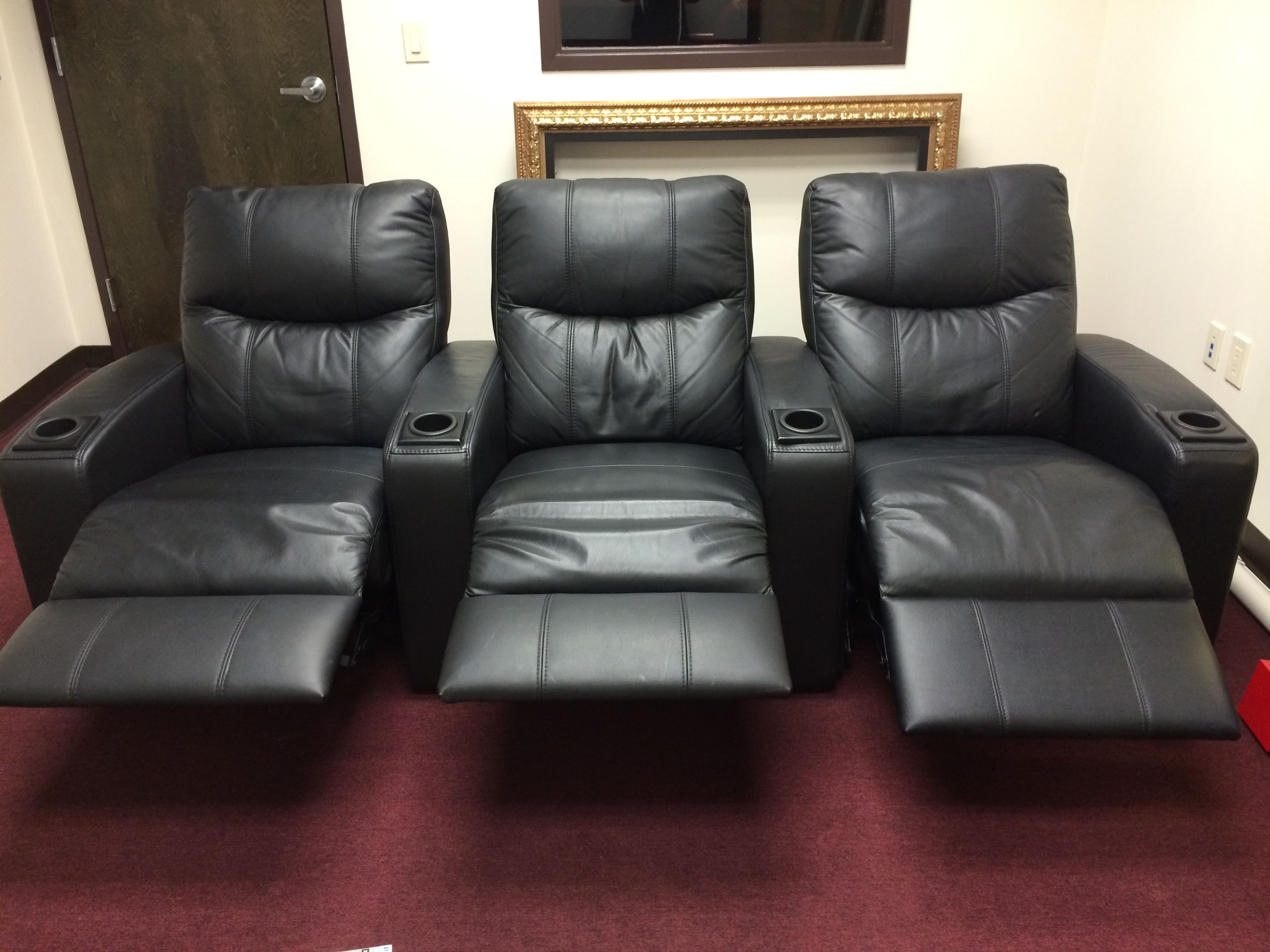 "Row of 3 Black, Leather Theater Chairs In great condition- one tiny little tear on bottom corner; easily hidden.   Made by Lovan; manual recline.   Cup holders for each seat.  Was $3695 new, SALE price $1200.   Dimensions:   94"" W x 39"" H x 38.5"" D Seated (53"" D; reclined)"