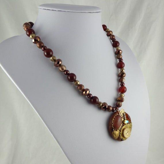 Photo of Collagenanhänger in Goldbraun – Perlenkette mit einem handgefertigten Anhänger aus Fimo und Assemblage, einschließlich eines Cabochons aus Goldstein