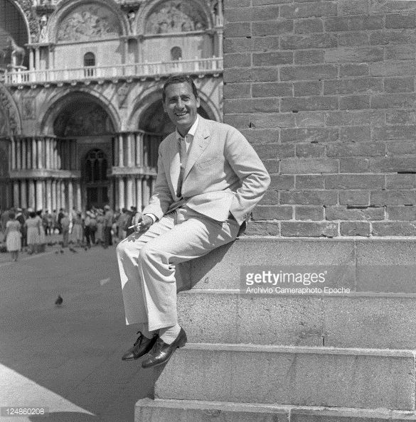 Italian actor Alberto Sordi, wearing a suit, portrayed while sitting on a corner of the bell tower in St. Mark Square, smoking a cigarette, Venice, 1959.