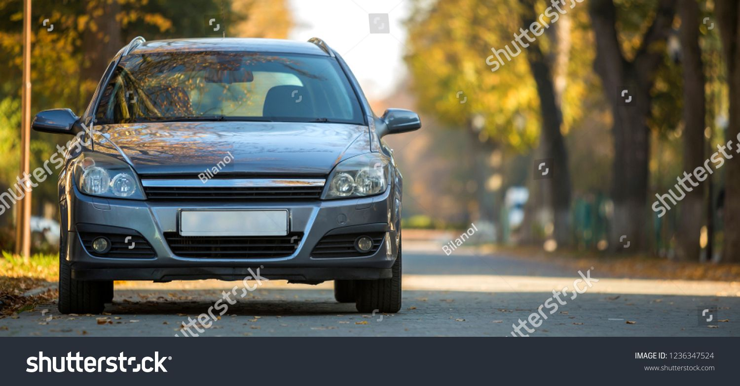 Front View Of Gray Shiny Empty Car Parked In Quiet Area On Wide Alley Under Big Trees On Blurred Green And Yellow Folliage Quiet Area Big Tree Bokeh Background
