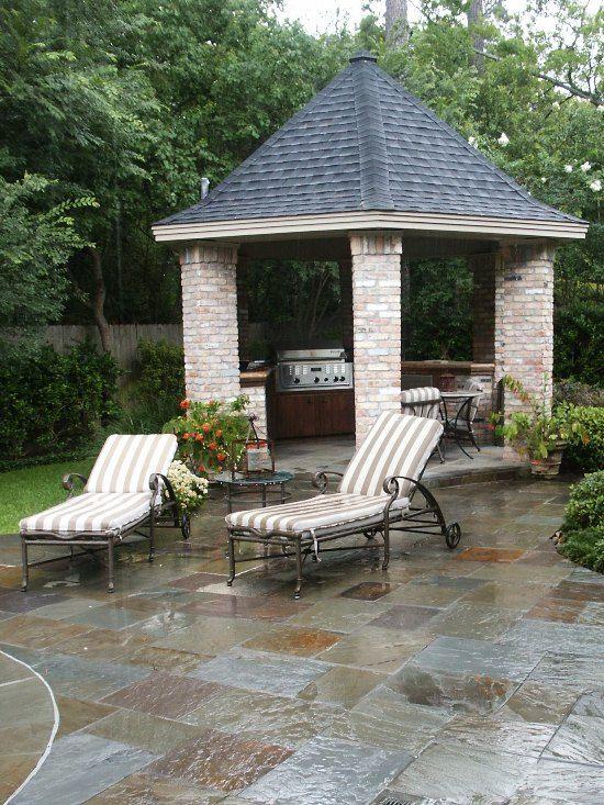 slate tile around pool with gazebo, outdoor kitchen, and brick