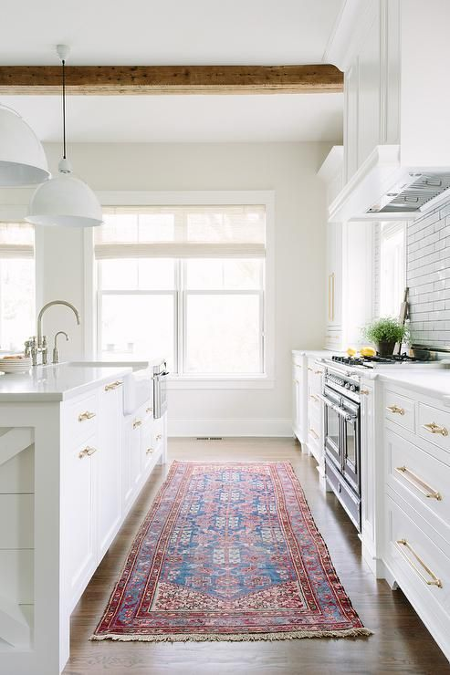 charming Red And White Kitchen Rugs Part - 3: Red and blue kilim rug covers wood floors framing a white kitchen island  fitted with a farmhouse sink accented with a polished nickel deck mount  gooseneck ...