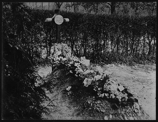 The grave of Manfred von Richthofen (1892-1918), a cavalry officer who became the most famous of all the World War I fighter pilots, bringing down a total of 80 Allied aircraft. He was shot down on 21 April 1918 and the British buried him in France with full military honours. The card on the nearest wreath bears tears the words, 'Royal Air Force'. [Original reads: 'Grave of German Airman - Baron Von Richthofen at Sailly le Sec, Somme.']