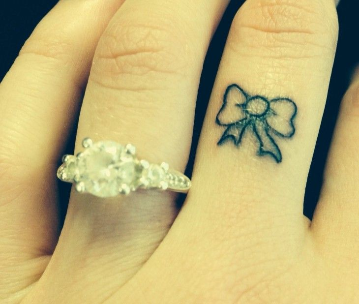 Tatouage discret petit nœud ruban sur un doigt