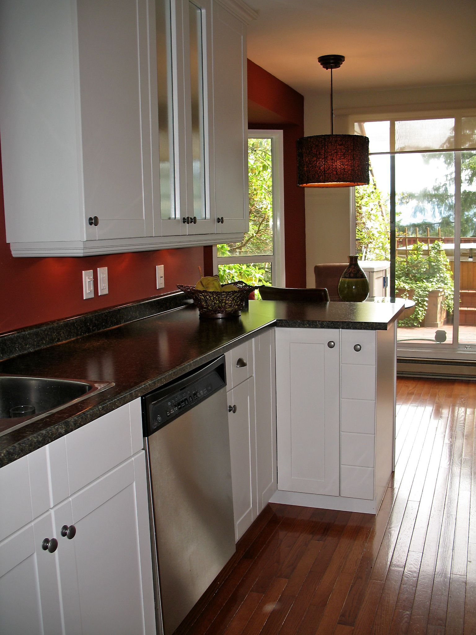 brick red walls with white cabinets and dark countertops ...