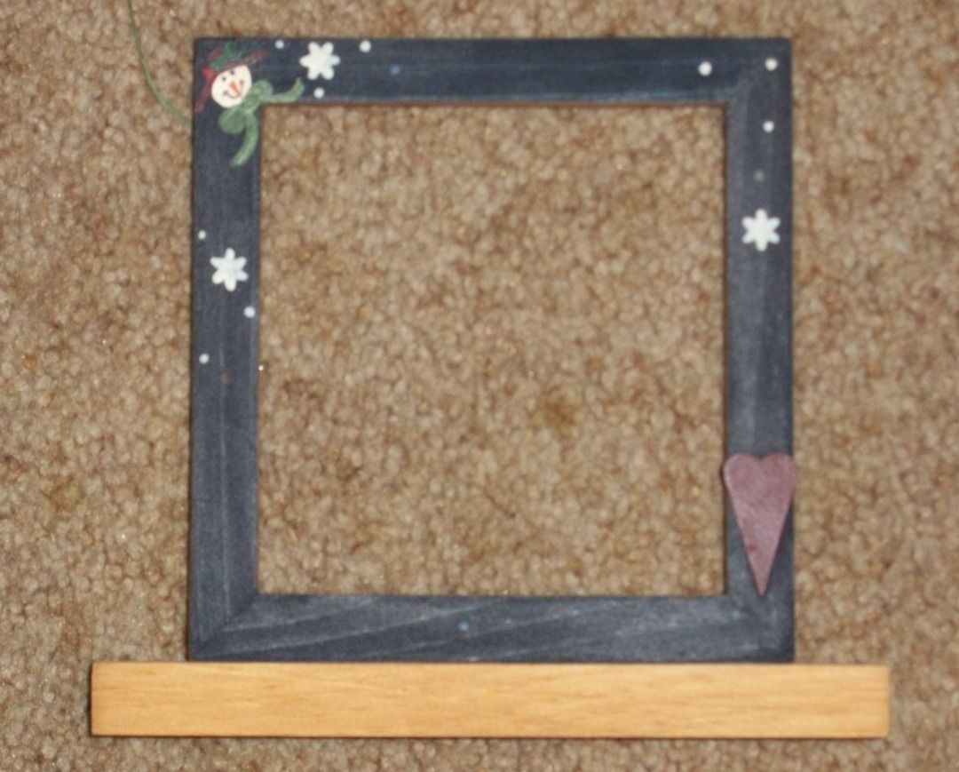 Blue decorative handpainted snowman frame with 3D red heart. It is on a wooden base so stand freely. Size is 5.25x5.5 opening, overall size 6.25x6.5 without base. Wooden base measures 5.25w x 1.5 deep and the overall height with base is 7.5 inches. Perfect for a winter project or photo.