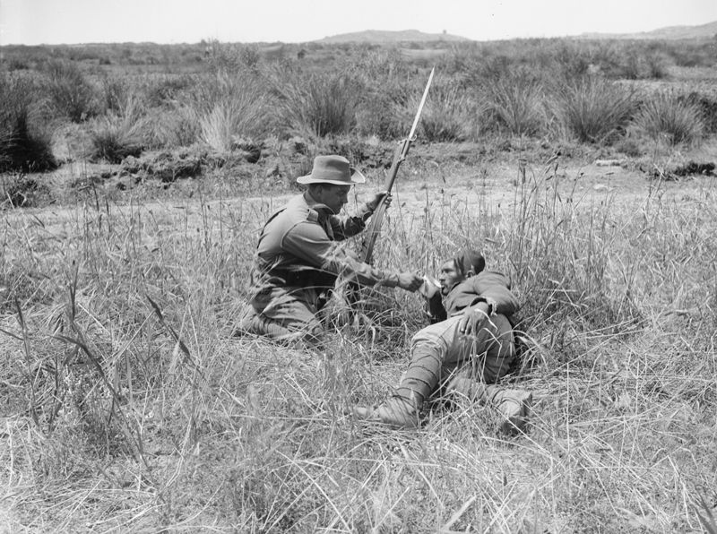 An Australian infantryman gives a drink to a wounded Turkish soldier during the Gallipoli Campiagn, 1915.