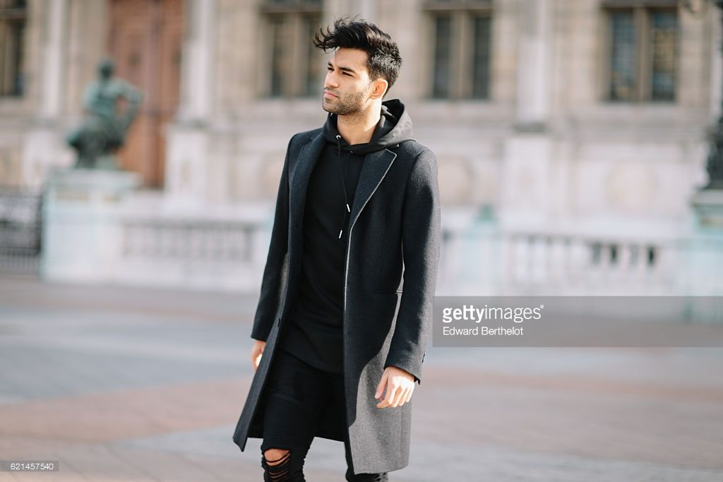 Anil Brancaleoni (Youtuber and professional gamer @WaRTeK), is wearing Bose QC35 silver headphones, a Sandro black long coat, a Maniere de Voir pull over, Maniere de Voir black ripped pants, Bocage black shoes, a Rolex watch, Ray Ban sunglasses, and a Lipault bag, at Hotel de Ville, in the 1st quarter of Paris, on November 6, 2016 in Paris, France.