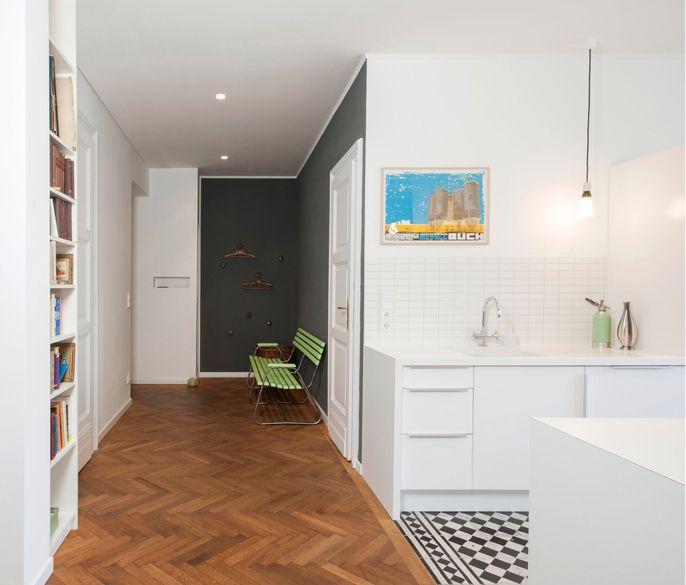 offene weiße Küche mit Fließenboden und Eichen- Fischgrätparkett