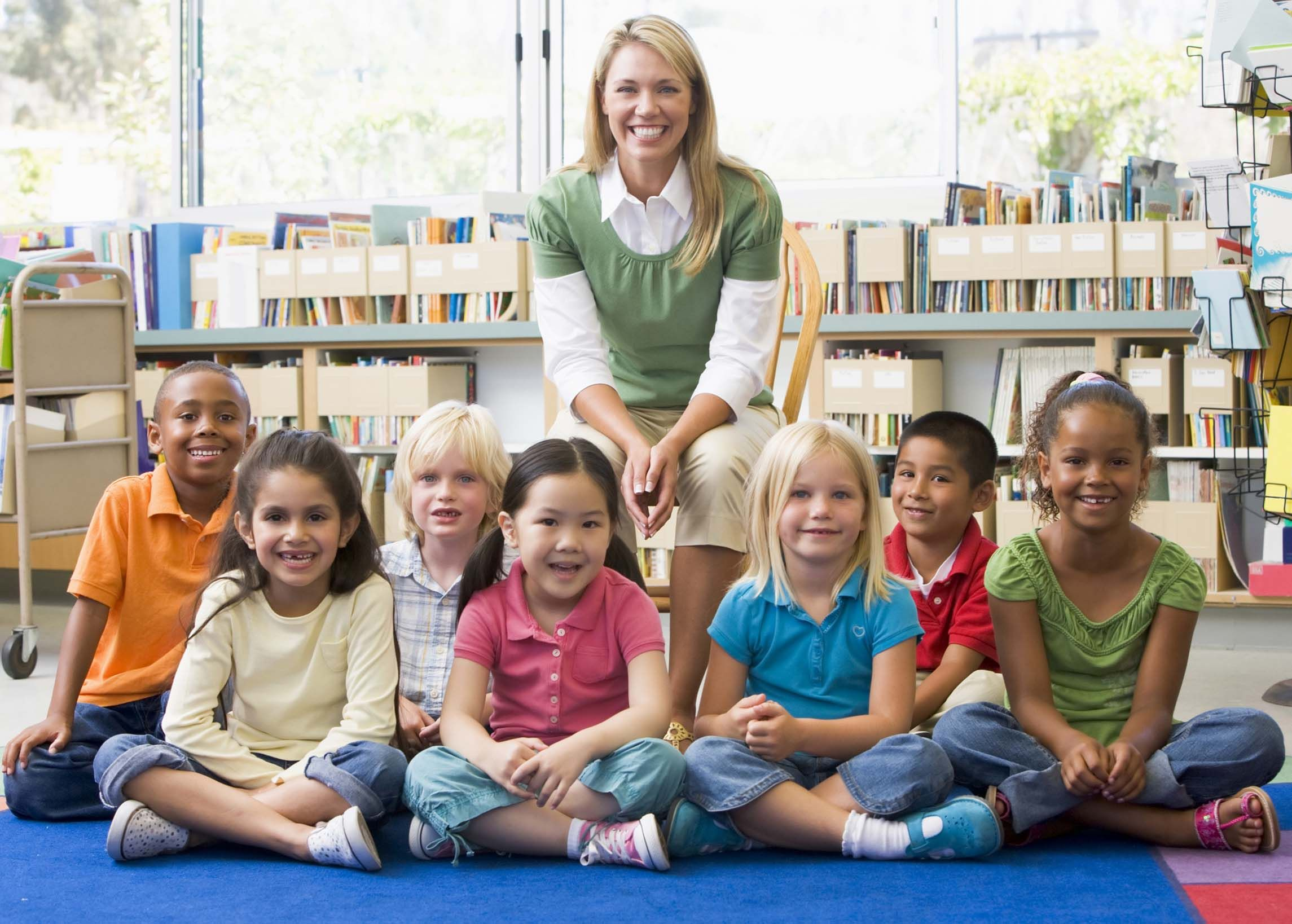 A Blonde Teacher Sits Smiling Behind Her Class Of Kindergarteners