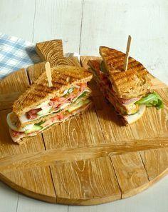 Lekker recept voor een club sandwich met gerookte kip, bacon, sla, tomaat, eii, pestmayonaise: deaal gerechtje tijdens de lunch.