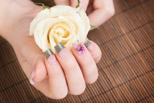 Nail art with glitter green, purple and pink nail polish.