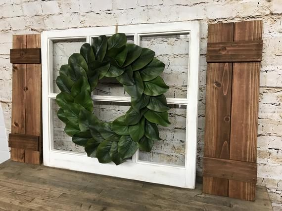 Photo of Farmhouse window frames with magnolia wreath and shutters made of plank and lath, 6-pane window frames in vintage style with magnolia wreath and shutters