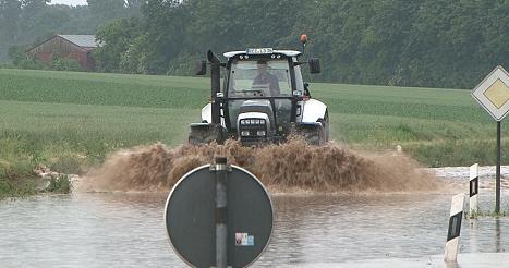 Ein Traktor fährt über eine überschwemmte Straße nach einem schweren Unwetter in Damme