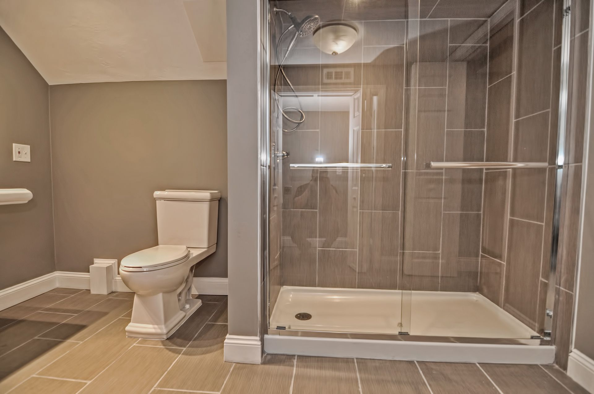 stand up shower floor to ceiling tile gray and white bathroom