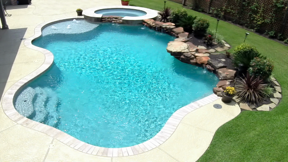 Its Thursday Weeping walls a raised spa with spillway tanning shelf with gushers and a great pgravel decking makes this custom swimming pool an instrument of fun and rela...