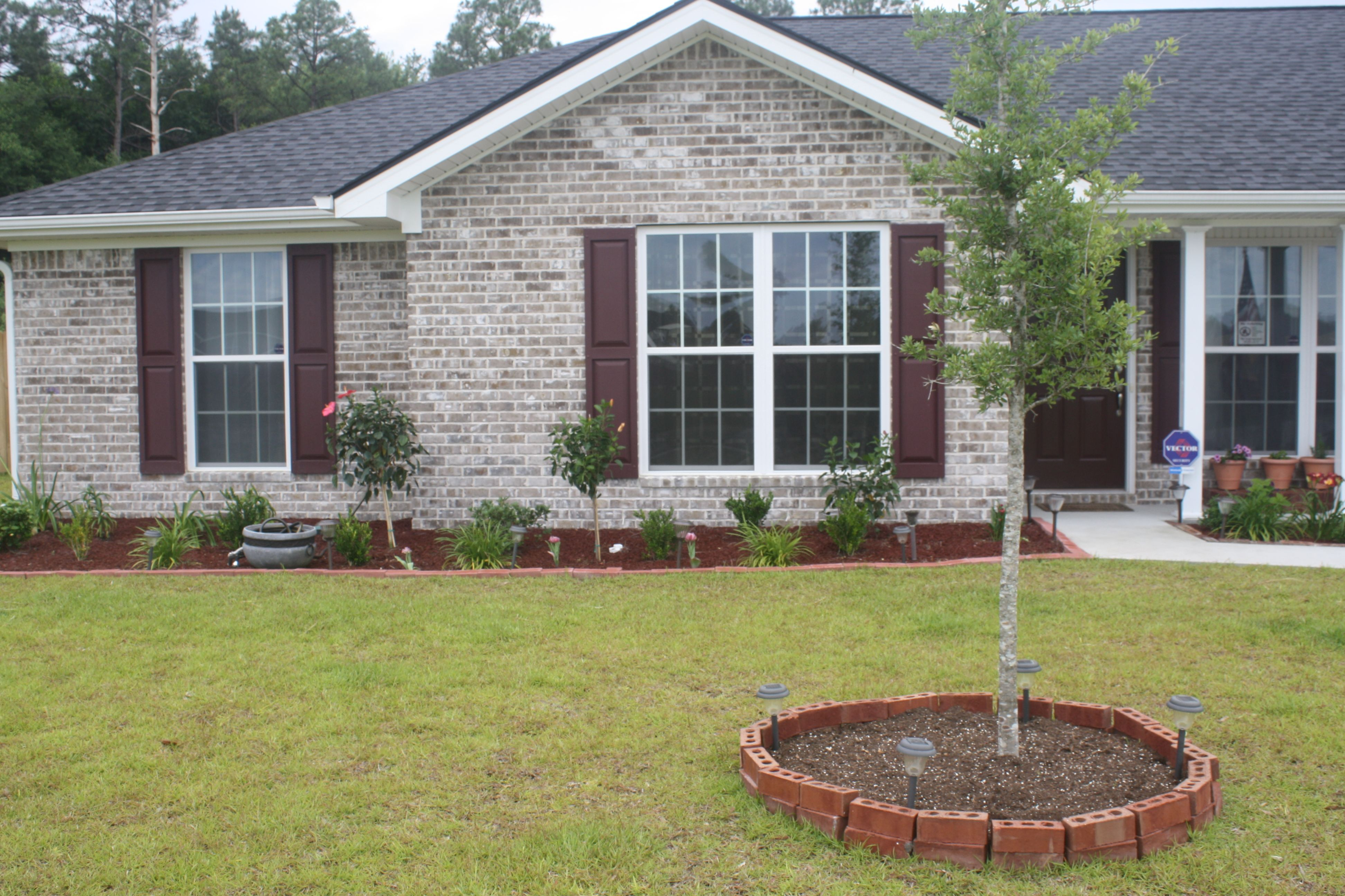 Border around flower beds and tree done with bricks from