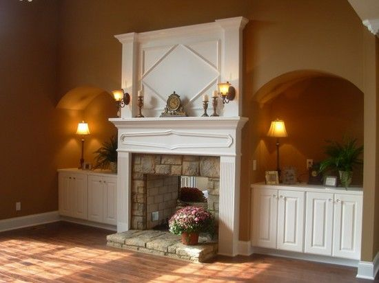 Attractive fireplace wall with nice wooden mantle and above mantle woodwork, recessed alcoves with storage cabinets, kighting and accessories, and the mantle shelf with small sconces an antique clock and candles. Heavy stone in the fireplace and hearth blend well with the wooden floors. Just add some comfortable furniture and it would be a very warm and inviting room!
