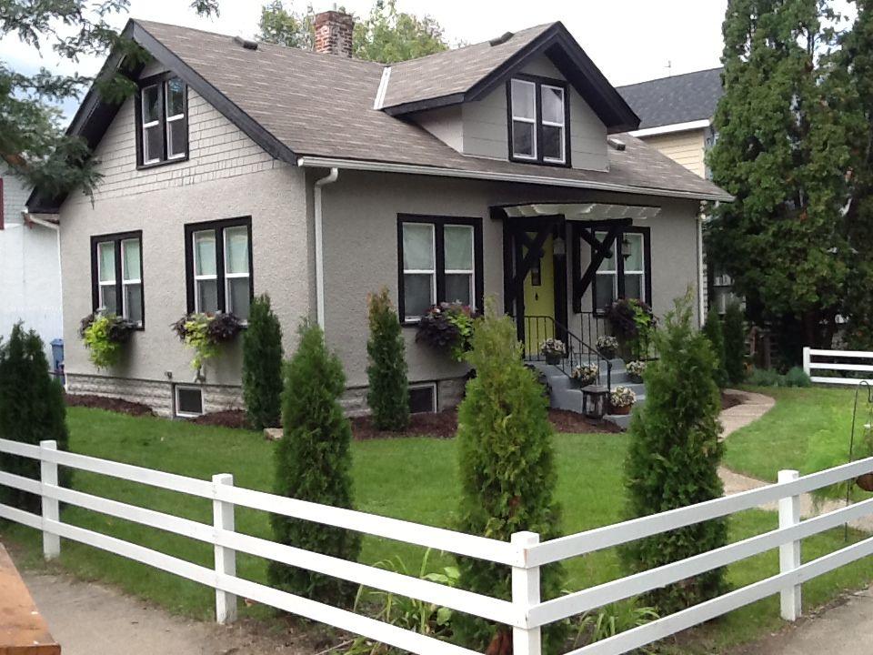 Remodeled 1918 craftsman home, black trim, taupe exterior, citron green  door, white