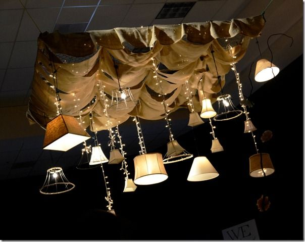 wedding chandelier statement piece made from either a king sized bed frame or a panel of chain link fencing, swagged with berlap, stripped with linen and/or musline and then laden with many different lamps/shades.......awesome