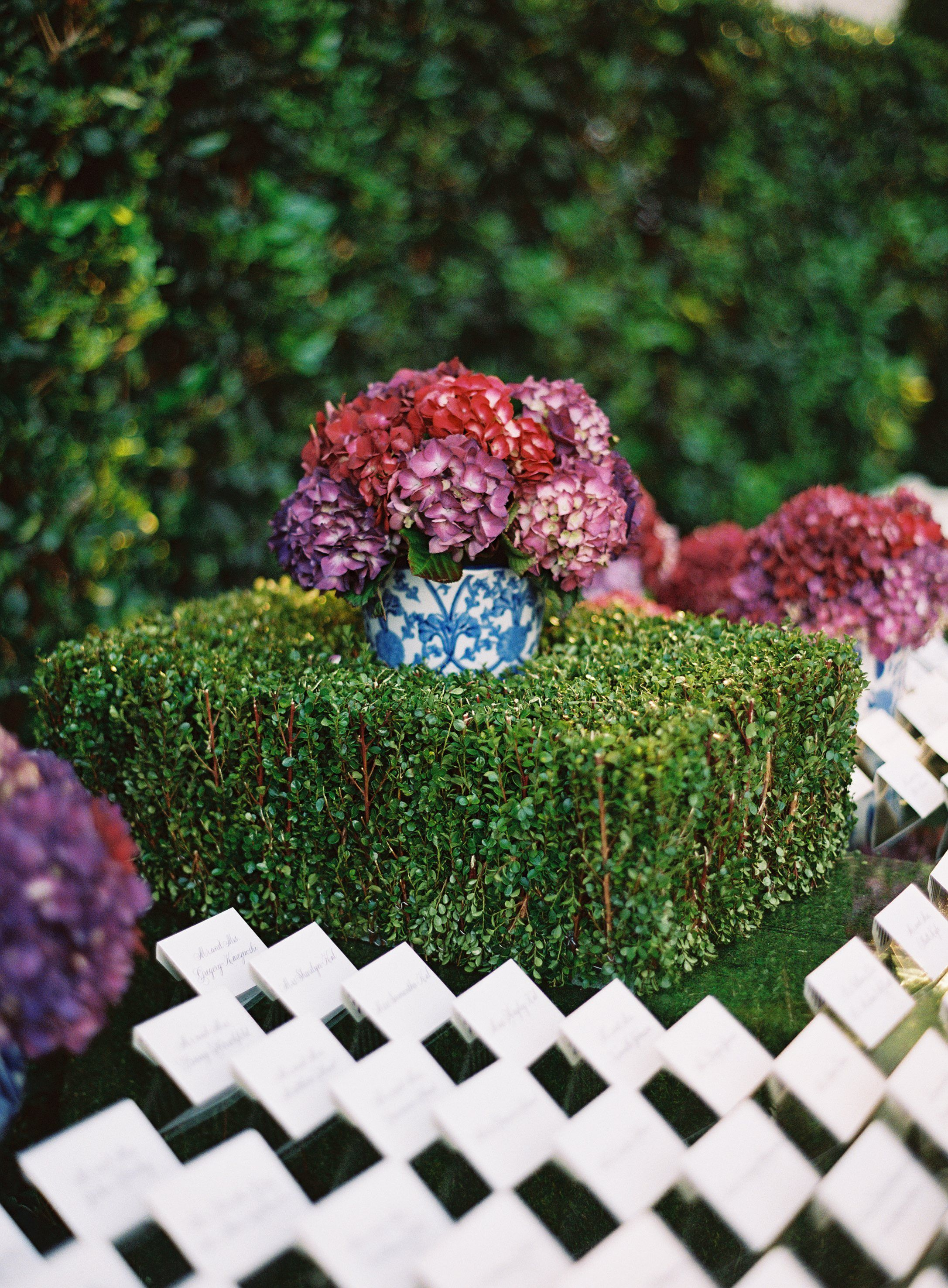 Red Hydrangea Arrangement Sitting on Manicured Hedge | Photography: Jose Villa Photography. Read More: http://www.insideweddings.com/weddings/incredible-rooftop-rehearsal-dinner-with-striking-striped-tent/555/