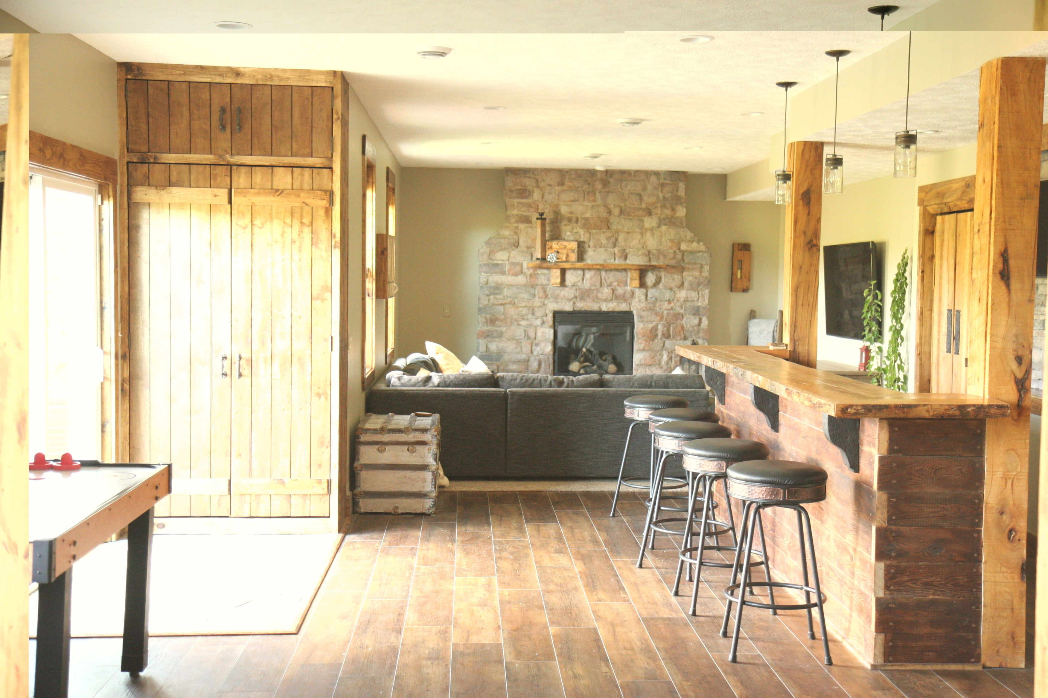 Rustic basement with custom barn wood doors, cabinets, and bar