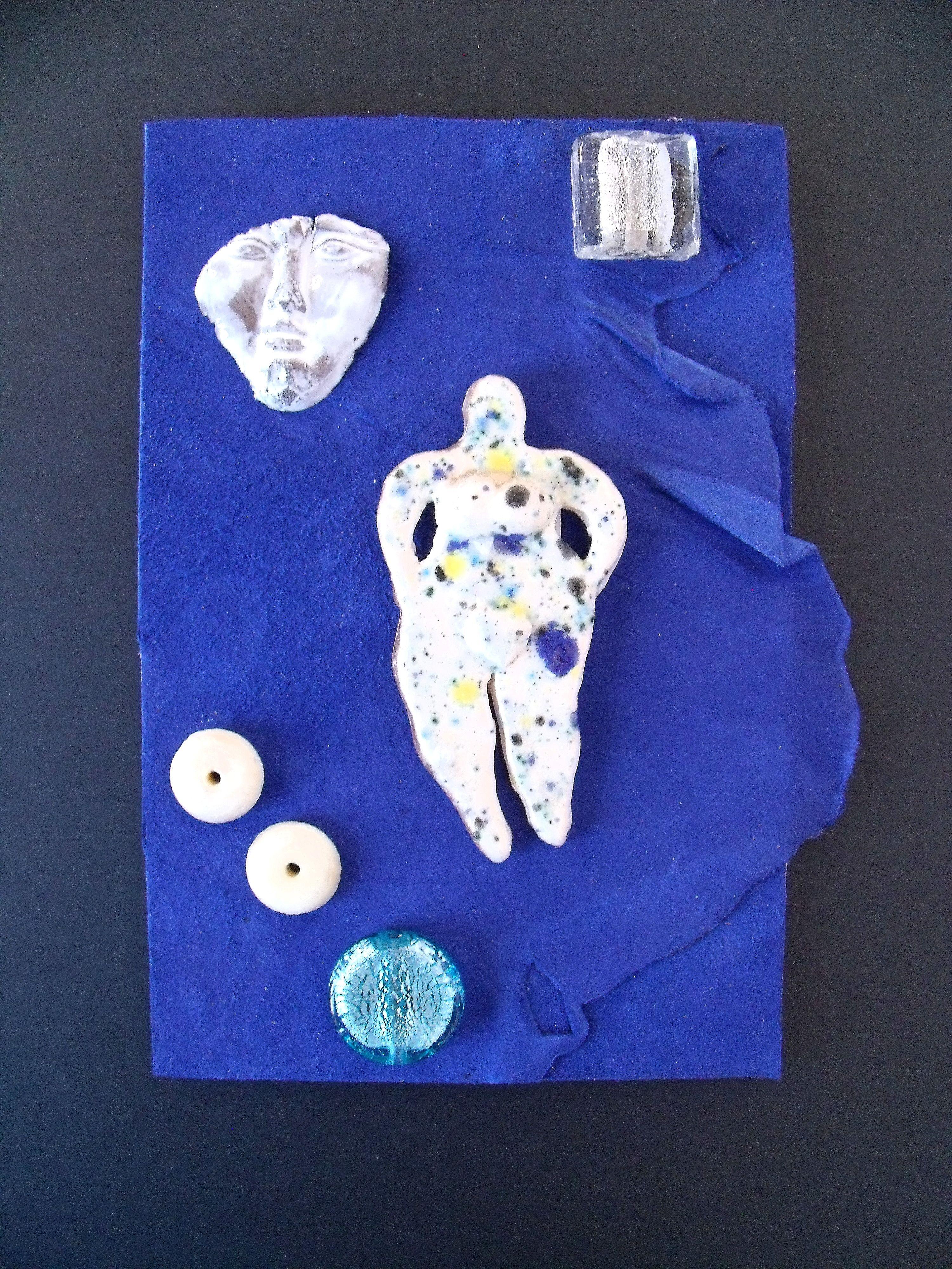 """Tableau d'un cuir bleu Klein collé sur une planchette de bois avec personnage central en céramique et perles.. """"Ma déchirure"""""""