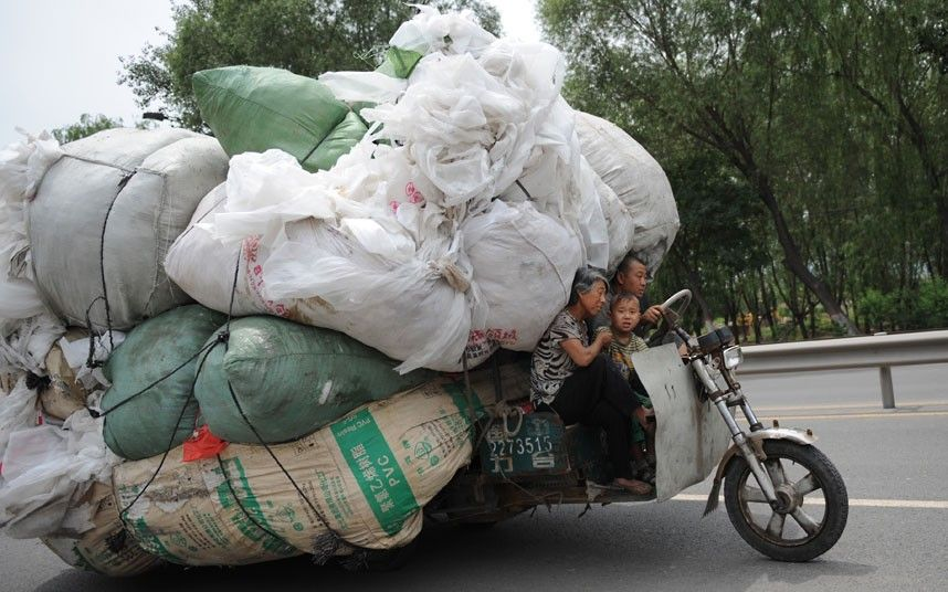 A family ride a heavily overloaded motor tricycle in Taiyuan china