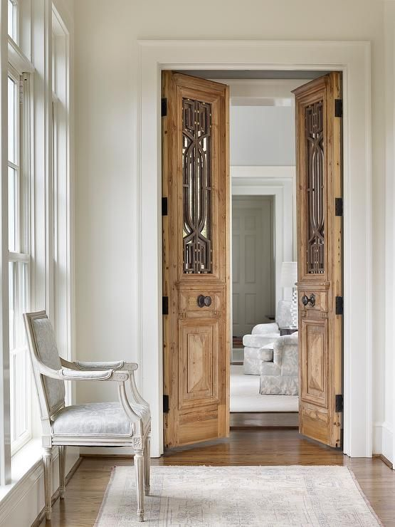 French Hallway Boasts A Light Gray French Chair Placed Atop A Faded Rug In Front Of Carved Wood